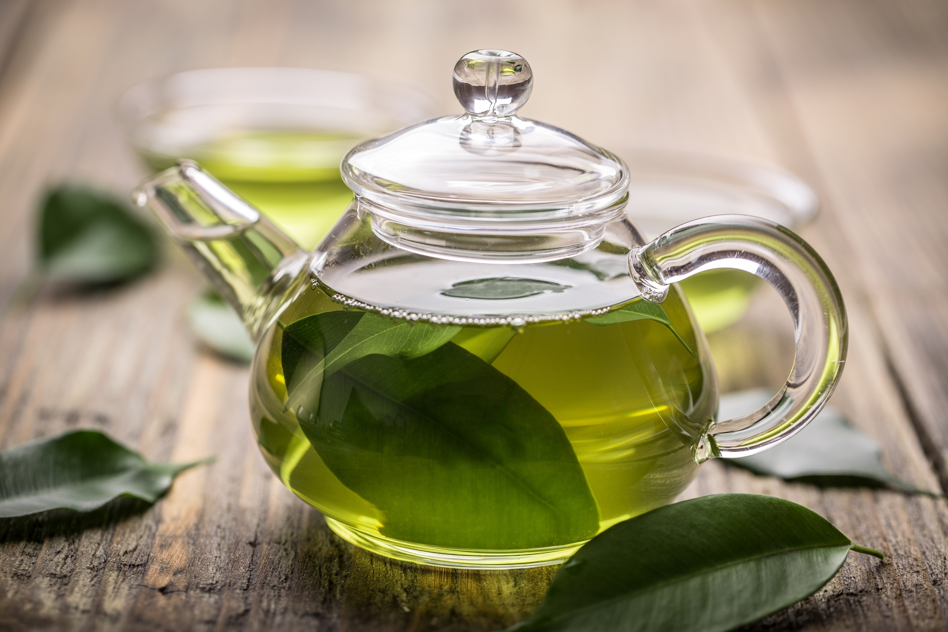 Glass teapot with green tea on wooden table